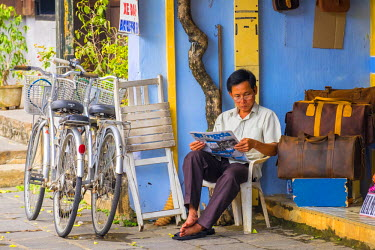 VIT1103AW Man reading a newspaper on the street in Hoi An, Quang Nam Province, Vietnam