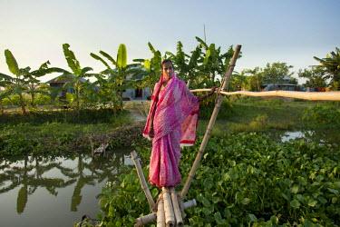BAN0014AW Jessore, Bangladesh. A female farmer crosses the bridge to her home.