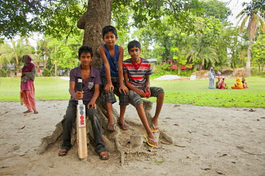 BAN0035AW Khulna, Bangladesh. A group of boys take a break from playing cricket in a public park.