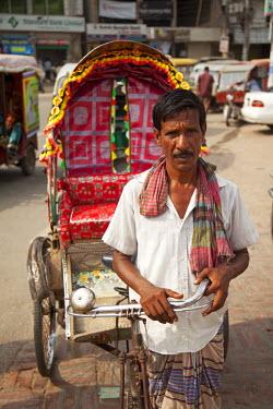 BAN0038AW Khulna, Bangladesh. A rickshaw rider takes a break.