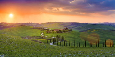 ITA5255AW Valdorcia, Siena, Tuscany, Italy. Panoramic view of a road of cypresses leading to a farmhouse with a stormy sunset in the background.