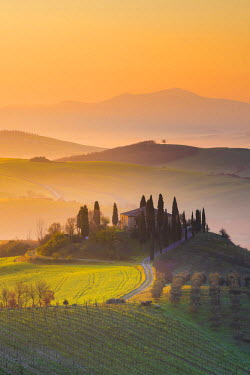 ITA5265AW Valdorcia, Siena, Tuscany, Italy. Tuscan farm on top of a hill at sunrise.