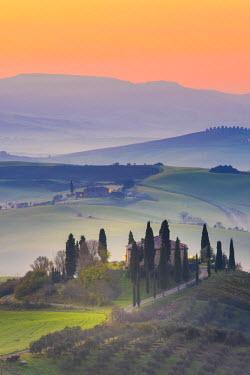 ITA5308AWRF Valdorcia, Siena, Tuscany, Italy. Tuscan farm on top of a hill at sunrise.