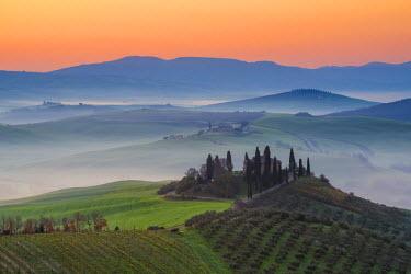 ITA5309AWRF Valdorcia, Siena, Tuscany, Italy. Tuscan farm on top of a hill at sunrise.