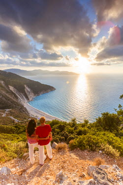 GRE1100AW Couple enjoying sunset over famous Myrtos beach. Kefalonia, Greek Islands, Greece (MR)