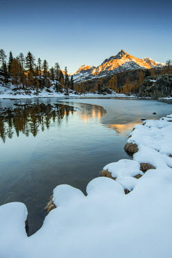 CLKFV37670 Sasso Moro peak at dawn reflects itself on the iced waters of Mufule Lake. Valmalenco, Valtellina, Sondrio, Lombardy, Italy, Europe.