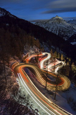 CLKFV37938 Car lights on the curvy Maloja Pass road at night. Maloja Pass, Engadin, Graubunden, Switzerland.