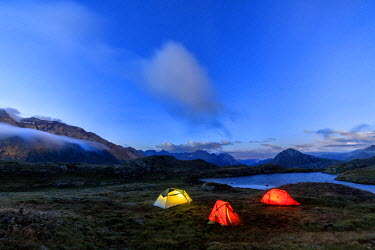 CLKRM32927 The soft lights of the tents light up dusk Minor Valley High Valtellina Livigno Lombardy Italy Europe