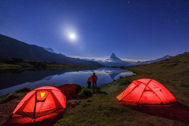 CLKRM33606 Lovers admire Matterhorn reflected in Lake Stellisee on a starry night of full moon Zermatt Valais Switzerland Europe
