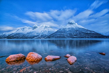 CLKRM36613 Blue sky at dusk and snowy peaks are reflected in the frozen sea at Oteren Storfjorden Lapland Lyngen Alps Tromsa� Norway Europe