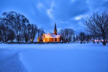 CLKRM36767 The illuminated church at dusk in the cold snowy landscape at Flakstad Lofoten Norway Europe