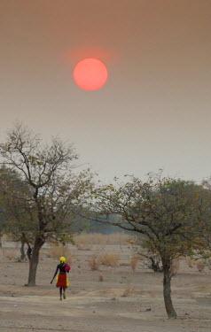 AF31BJA0462 Africa, Namibia, Opuwo. Himba woman walking at sunset.