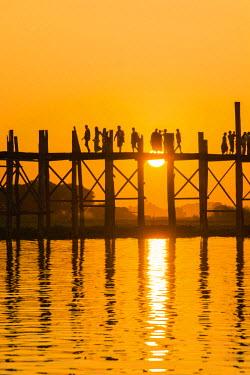 AS06IHO0326 Myanmar. Mandalay. Amarapura. U Bein Bridge. Tourists walking on the bridge at sunset.