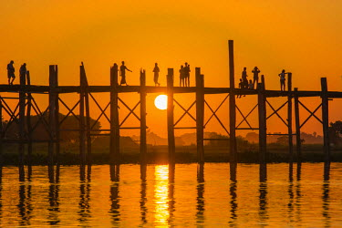 AS06IHO0327 Myanmar. Mandalay. Amarapura. U Bein Bridge. Tourists walking on the bridge at sunset.