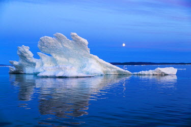 CN15PSO0109 Canada, Nunavut Territory, Moon rises behind melting iceberg in Frozen Channel at northern edge of Hudson Bay near Arctic Circle