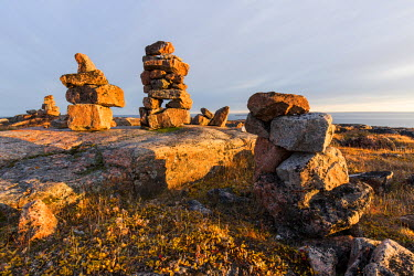 CN15PSO0131 Canada, Nunavut, Territory, Setting sun lights stone cairns on Harbour Islands along Hudson Bay near Arctic Circle