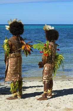 OC12CMI0025 Melanesia, Papua New Guinea, Tufi. Two young women in traditional sing-sing native attire. Tufi is well known for its use of tropical bird feathers, seashells, and tapa cloth in their elaborate costum...