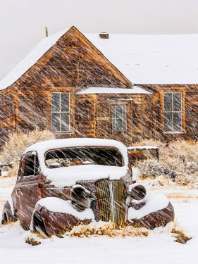 US05BJY0334 USA, California, Bodie. Abandoned car and building in snowfall.