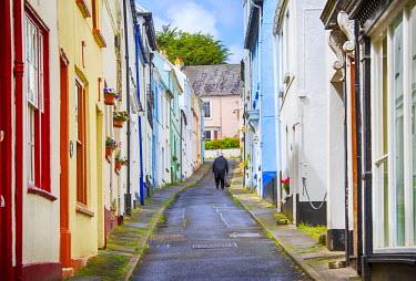 ENG12905AW England, Devon, Appledore. An elderly man walking up a colourful steep street.