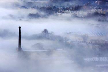 England, Halifax. Mill chimney and houses appearing through mist.