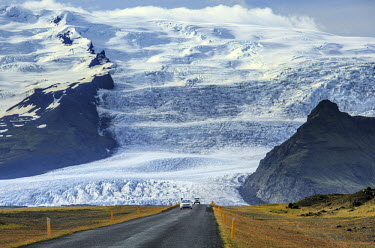 ICE3577AW Iceland, Eastern Region. Cars on Route 1 with the Vatnajokull ice cap behind.