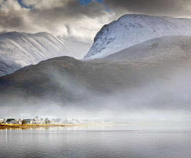 SCO33845AW Scotland, Fort William. Ben Nevis towering above the village of Caol whilst mist rises from Loch Linnhe.