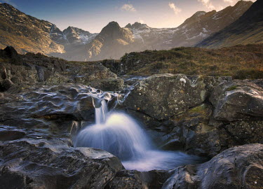 SCO33925AW Scotland, Isle of Skye. The Fairy Pools stream and waterfall with the Cuillin Mountains behind.
