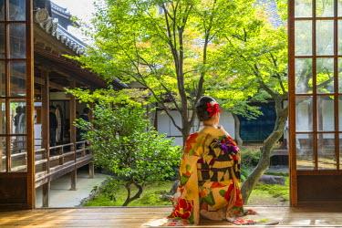 JP03770 Woman looking out onto Zen garden, Kyoto, Japan