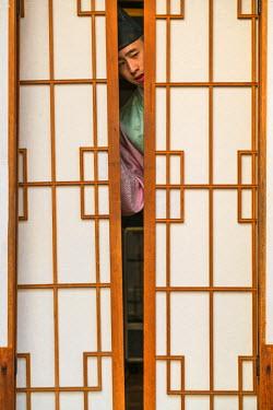 KR01277 Man in traditional dress coming through doors of traditional house, Seoul, Korea