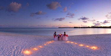 MIV0293AW Couple dining on beach at Olhuveli Beach and Spa Resort at sunset, South Male Atoll, Kaafu Atoll, Maldives (PR + MR)