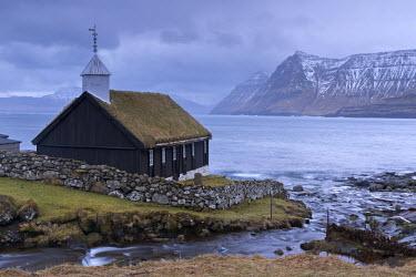 DEN0267AW Grass roofed Church in the village of Funningur on the island of Eysturoy, Faroe Islands, Denmark, Europe. Winter (April) 2015.
