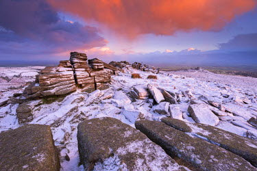 ENG13258AW Colourful sunrise above snow covered moorland, Belstone Tor, Dartmoor, Devon, England. Winter (January) 2016.