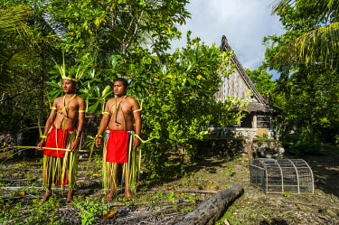OC18MRU0146 Traditional dressed men standing in front of a traditional house on the island of Yap, Micronesia