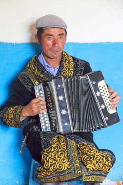 AS25EWI0114 Asia, Western Mongolia, Bayan Olgii Province, Khara Khoto, near Tolbo village. Kazakh man playing traditional melodies on an accordion
