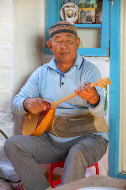 AS25EWI0118 Asia, Western Mongolia, Bayan Olgii Province, Khara Khoto, near Tolbo village. Kazakh man plays the Topshur, a two stringed lute, used to play songs and tell stories via music, in Western Mongolia