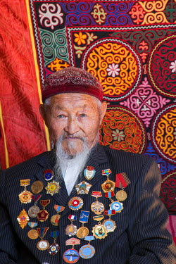 AS25EWI0147 Asia, Western Mongolia, Bayan-Olgii. Baytolda, one of the oldest living Golden Eagle hunters. He is more than 90 years old. He shows off his medals received from the Russian army for service in WWII