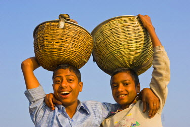 AS03MRU0115 Young boys carrying baskets on their heads in the Unesco World Heritage Site Sundarbans, Bangladesh, Asia