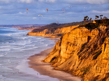 US05ACO0024 USA, California, La Jolla. Paragliders float over Black's Beach in late afternoon