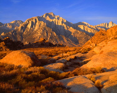 USA, California, eastern Sierra Nevada Mountains, Sunrise on Lone Pine Peak (center, 12,944 feet) and Mt. Whitney (right, 14,495 feet) above rocks of the Alabama Hills