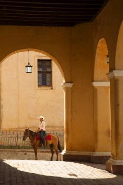 CA11JME0168 Cuba, Trinidad, woman riding horse viewed through arch of cathedral, Trinidad and the Valley de los Ingenios is a UNESCO World Heritage Site