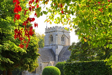 ENG13312AW England, Oxfordshire, Minster Lovell. St Kenelms Church framed by colourful leaves.