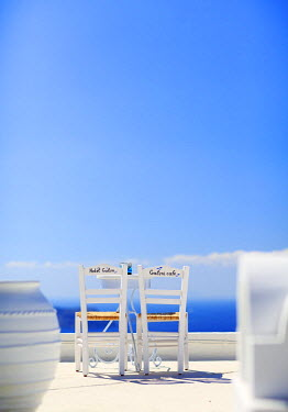 GRE1196AW Greece, Santorini, Firostefani. Table and chairs overlooking the caldera at Hotel Galini.