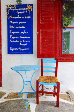 GRE1256AW Greece, Amorgos, Chora. Table and chair outside a taverna.