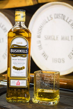 NIR8858AW United Kingdom, Northern Ireland, County Antrim, Bushmills. A Whisky bottles and glass in The Old Bushmills Distillery, the oldest working distillery in Ireland.