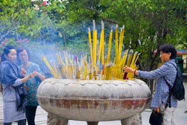 HMS1826724 China, Hong Kong, Lantau Island, Ngong Ping, Monastery of Pol Lin, believer putting depositing sticks of incense