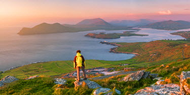 IRL0455AW Valentia island (Oilean Dairbhre), County Kerry, Munster province, Ireland, Europe. Panoramic view of a man watching sunset from the Geokaun mountain and Fogher cliffs.