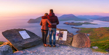 IRL0456AW Valentia island (Oilean Dairbhre), County Kerry, Munster province, Ireland, Europe. Panoramic view of a couple watching sunset from the Geokaun mountain and Fogher cliffs.