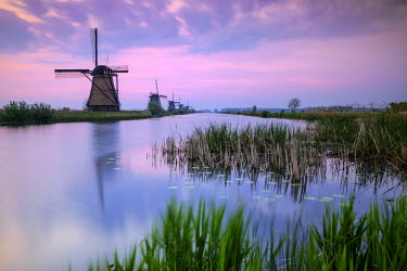 CLKRM39204 Sky is tinged with purple at dawn on the windmills reflected in the canal Kinderdijk Rotterdam South Holland Netherland Europe