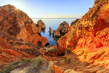 CLKRM40001 Golden sunrise on the  red cliffs of Ponta da Piedade Lagos Algarve Portugal Europe
