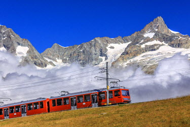 CLKRM40085 The Bahn train on its route with high peaks and mountain range in the background Gornergrat Canton of Valais Switzerland Europe